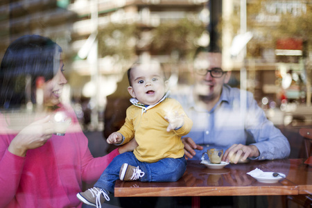 shop window: Baby boy sitting on table in a coffee shop looking through windowpane