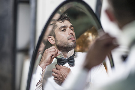 Man looking in mirror adjusting collar LANG_EVOIMAGES