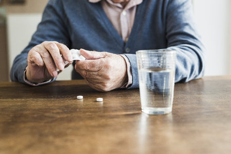 man drinking water: Hands of senior man taking tablets out of blister pack, close-up