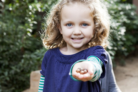 likeable: Portrait of blond little girl with a hand full of nuts