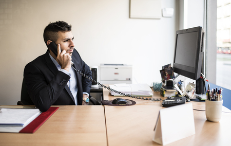 Man on the phone at desk in office