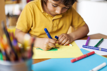 children painting: Little boy drawing on yellow paper LANG_EVOIMAGES