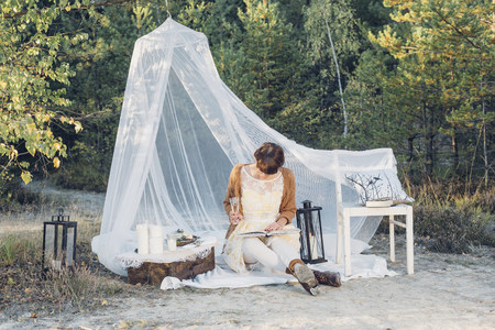 Woman reading a book in a romantic camp in autumnal nature