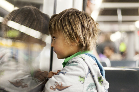 Little boy looking through window of a subway train LANG_EVOIMAGES