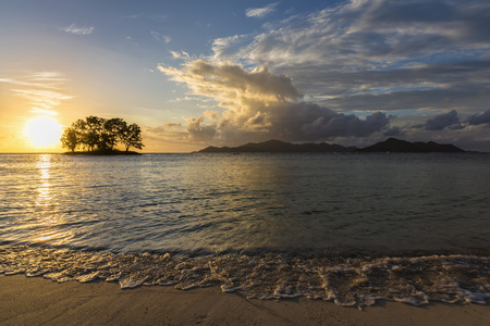 Seychelles, La Digue, Anse Source DArgent, Praslin Island in the background, small island with trees at sunset