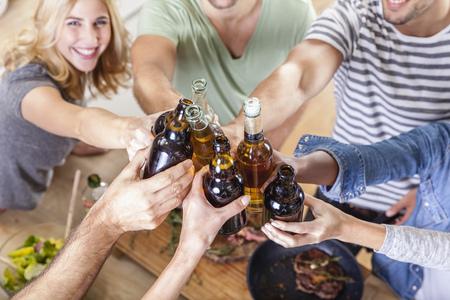 Friends clinking beer bottles in kitchen LANG_EVOIMAGES