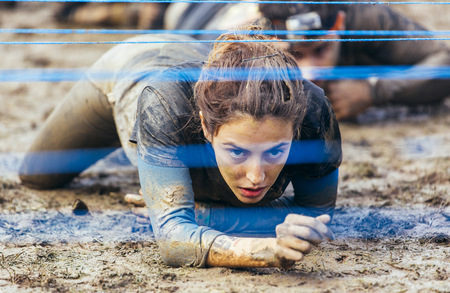 conquering adversity: Participants in extreme obstacle race crawling under electric wire