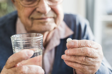 man drinking water: Hands of senior man holding tablet and glass of water, close up LANG_EVOIMAGES