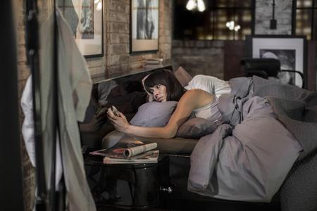 Woman sleepless in bed looking at alarm clock