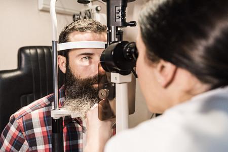 Optometrist examining eyes of a bearded man LANG_EVOIMAGES