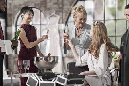 marrying: Bride getting ready for wedding clinking champagne glass with her mother