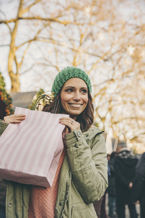 Happy woman holding a gift bag on the Christmas Market LANG_EVOIMAGES