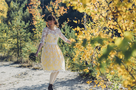 Portrait of dancing young woman with bouquet in autumnal nature
