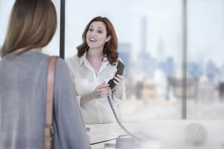 Office receptionist on the phone talking to guest