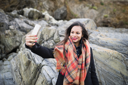 Spain, Ferrol, portrait of smiling  woman taking a selfie with her smartphone in front of rocks