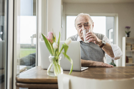 man drinking water: Portrait of senior man with laptop drinking glass of water at home