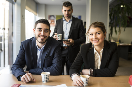 Portrait of smiling man and woman sitting at office desk with coffee