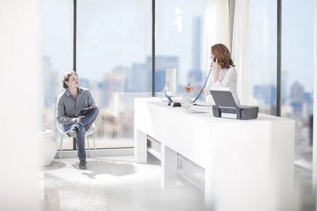 Office receptionist on the phone and man on chair