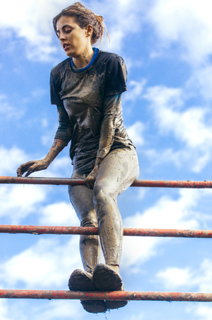 conquering adversity: Participants in extreme obstacle race climbing over hurdle