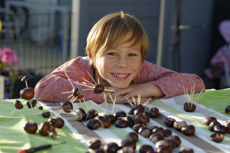 tinkered: Portrait of happy little boy with tinkered chestnut figurines LANG_EVOIMAGES