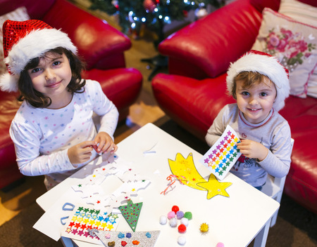 Portrait of two little girls tinkering Christmas decoration