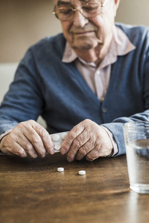man drinking water: Senior man taking tablets out of blister pack, close-up