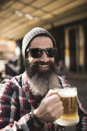 Portrait of smiling hipster with beer foam moustache at outdoor gastronomy LANG_EVOIMAGES