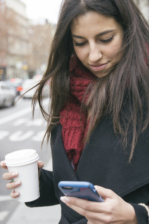go shopping: Spain, young woman with coffee to go looking at her smartphone
