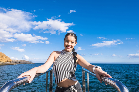Spain, Tenerife, portrait of smiling young woman in front of the sea LANG_EVOIMAGES