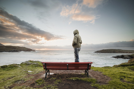 Spain, Ferrol, man wearing hooded jacket standing on a bench at the coast looking at distance