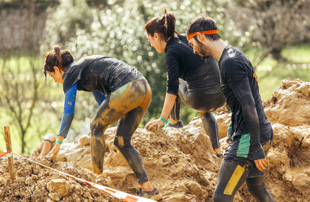 Participants in extreme obstacle race, running through mud LANG_EVOIMAGES