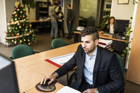 Man working at desk in office with Christmas tree in background LANG_EVOIMAGES