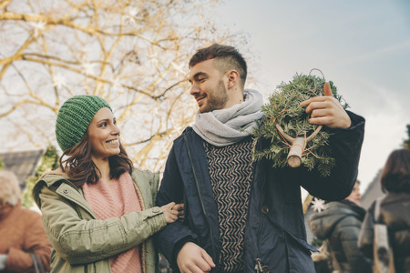 incidental people: Happy couple with a tree walking over the Christmas Market