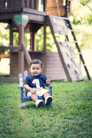 Baby boy sitting on chair on a meadow of a playground