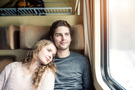 Smiling young couple in train car looking out of window