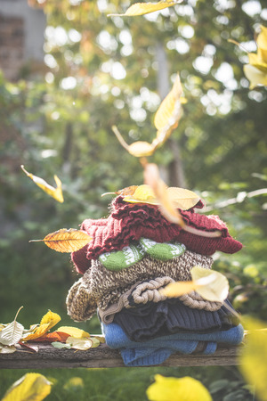 Stack of warm clothing and falling autumn leaves LANG_EVOIMAGES