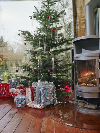 fireplace: Christmas presents under Christmas tree next to cozy fireplace
