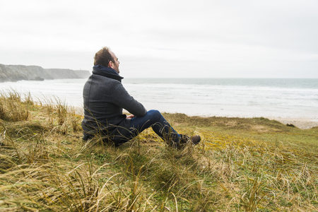 France, Bretagne, Finistere, Crozon peninsula, man sitting at the coast LANG_EVOIMAGES