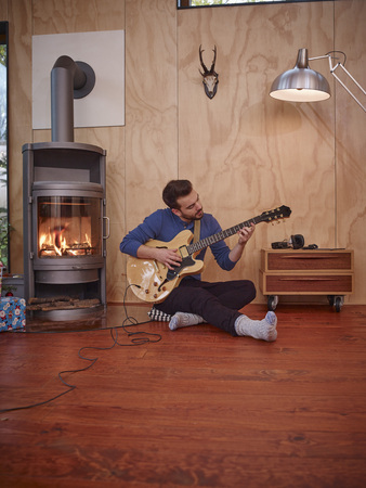 fireplace: Young man sitting by fireplace, playing guitar LANG_EVOIMAGES