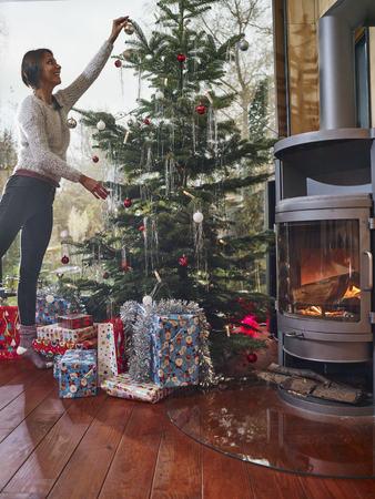 fireplace: Woman decorating Christmas tree
