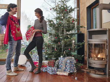 fireplace: Couple standing in front of Christmas tree unwrapping Christmas jumper LANG_EVOIMAGES