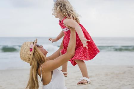 Brasil, Rio de Janeiro, mother lifting up daughter on Copacabana beach