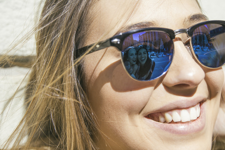 ardor: Friends of young woman reflecting at her sunglasses LANG_EVOIMAGES