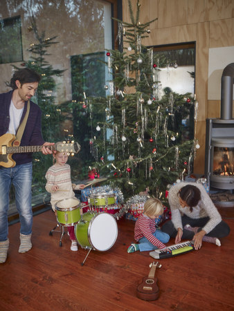 fireplace: Family playing music together under Christmas tree LANG_EVOIMAGES