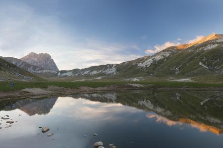 Italy, Abruzzo, Gran Sasso e Monti della Laga National Park, plateau Campo Imperatore, Corno Grande peak reflected in lake Petranzoni at sunset