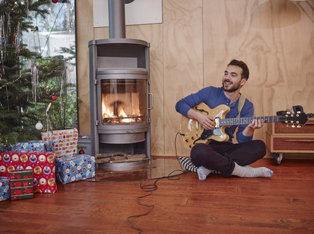 fireplace: Man sitting on floor and playing electric guitar by Christmas tree LANG_EVOIMAGES