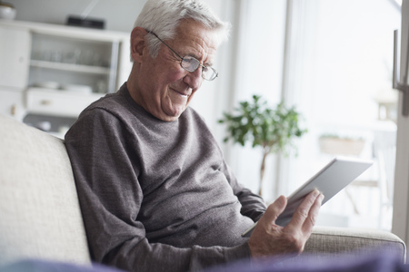 likeable: Portrait of senior man sitting on couch at home using digital tablet