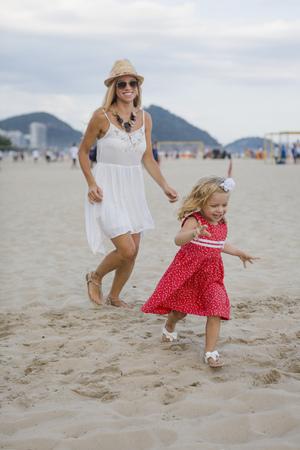 sandalias: Brasil, Río de Janeiro, feliz madre e hija corriendo en la playa de Copacabana LANG_EVOIMAGES