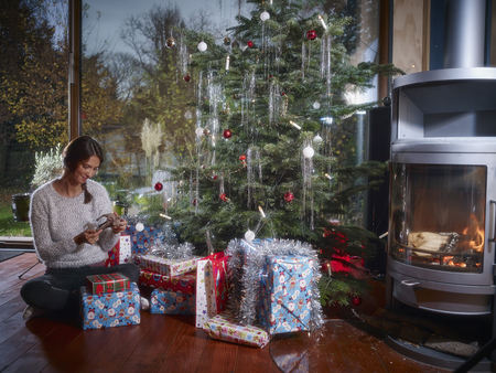 fireplace: Woman unwrapping Christmas gifts under Christmas tree