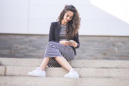 vestidos de epoca: Retrato de adolescente sentado en pasos mirando su teléfono inteligente